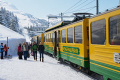 People walk by the Wengernalpbahn railway platform in Grindelwald, Switzerland. Stock Image