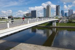 People walk by the white bridge in Vilnius, Lithuania. VILNIUS, LITHUANIA - MAY 04, 2015: Unidentified people walk by the white bridge in Vilnius, Lithuania Royalty Free Stock Photo