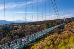 People walking on Mishima Skywalk bridge with Mount fuji seen in the distant, clear day. People walking on Mishima Skywalk bridge with Mount fuji seen in the royalty free stock photography