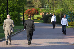 People Walking. Photo of people walking in a pedestrianised urban area with parkland around Royalty Free Stock Images