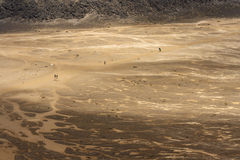 People walking accros barren land at Tongariro National Park Stock Photography