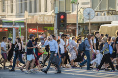 People walking across a busy crosswalk. Melbourne, Australia - Dec 16, 2015: People walking across a busy crosswalk in downtown Melbourne at sunset Royalty Free Stock Photography