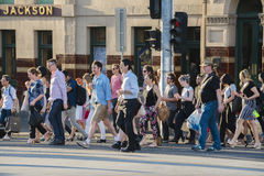 People walking across a busy crosswalk in Royalty Free Stock Images