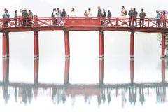 People walking across Huc Bridge, Vietnam. Royalty Free Stock Images