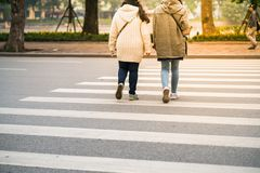 People walking across a street in Hanoi, Vietnam. Closeup.  Stock Images