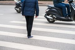 People walking across a street while motorbikes keep running on street in Hanoi, Vietnam. Closeup.  Royalty Free Stock Photos