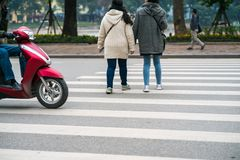 People walking across a street while motorbikes keep running on street in Hanoi, Vietnam. Closeup.  Stock Photography