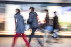 People walking against shop window at dusk, zoom effect, motion Royalty Free Stock Image