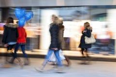 People walking against shop window at dusk, zoom effect, motion Stock Image
