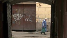 People walking beside aged building. stock video footage