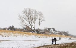 People walking along on Baltic sea beach of village names Ahrenshoop Mecklenburg-Vorpommern, Germany in winter time with snow royalty free stock photo