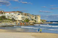 People walking along the beach and apartments in Sydney. Sydney, Australia - June 25, 2016: View of people walking along the beach and modern apartments at Bondi Royalty Free Stock Photography