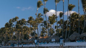 People walking along the beach on tropical resort. Tilt shot of people walking on the beach on a windy day, sky and palm trees at the end stock footage