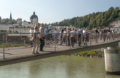 People walking. Along the bridge in the river Salzach. You see  along the shore. It is a editorial image on a sunny day. You can see the cathedral in the royalty free stock photography