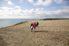 People Walking Along Coastal Cliff Stock Photos