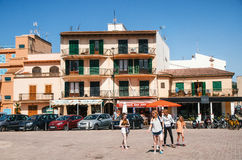 People walking along at historical town part of Alcudia with its traditional house and cafe royalty free stock images