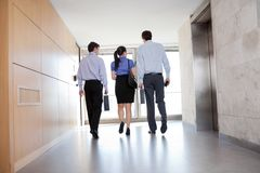 People Walking Along Office Corridor royalty free stock photography