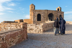 People walking along old ramparts of Essaouira, Morocco Royalty Free Stock Images