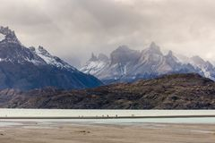 People walking along path during low tide in Glacier Gray, beautiful mountain range with snow in the background. Torres del Paine,. People walking along path Royalty Free Stock Photos
