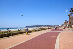People Walking Along Paved Promenade on Beach Front Royalty Free Stock Photography