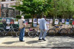 People walking along reading posters in Cambridge Stock Images