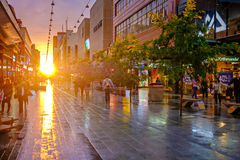 People walking along the Rundle Mall at sunset. Adelaide, Australia - September 30, 2016: People walking along the Rundle Mall in Adelaide CBD at sunset, viewing Stock Image