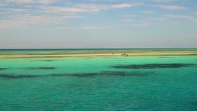 People walking along the sandy little island in the open sea stock footage