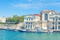 People walking along the sea front in Sevastopol. SEVASTOPOL, CRIMEA - MAY 7, 2014: People walking along the sea front and excursion boats waiting for tourists Royalty Free Stock Photography