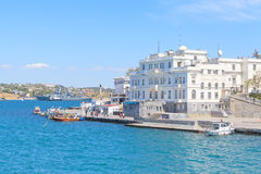 People walking along the sea front in Sevastopol. SEVASTOPOL, CRIMEA - MAY 7, 2014: People walking along the sea front and excursion boats waiting for tourists Royalty Free Stock Image