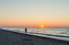 People walking along the seashore during the dawn.  royalty free stock images