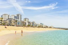 People walking along seaside in Quarteira during sunny day, Alga royalty free stock photography