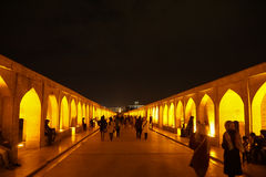 People walking along the Si-o-se Pol in Isfahan, Iran. Isfahan,Iran - October 28,2015:People walking along the Si-o-se Pol in Isfahan, Iran at night. It was stock photography