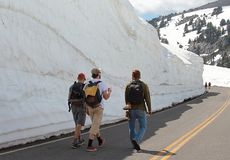 People are walking along the snow drift in the middle of summer royalty free stock photography