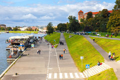 People are walking along the Vistula river bank in the historic city center of Krakow, Poland Royalty Free Stock Image