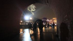 People is walking through the arch. On a rainy night stock video