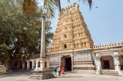People walking around famouse Hindu temple with carved gopuram gates Royalty Free Stock Photo
