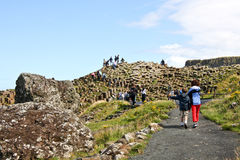 People walking around Giants Causeway and Cliffs, Northern Ireland Royalty Free Stock Images