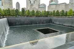 People walking around one of the 9/11 memorial pools in New York City stock photos