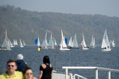 People walking at baldeneysee in essen germany. People walking at lakeside watching sailing boats having a race in essen germany stock photography
