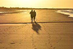 People walking on the beach at dawn Algarve Portugal. Algarve, Portugal - September 27, 2016: Elderly couple walking on the beach of Monte Gordo silhouetted royalty free stock photography