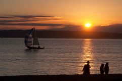 People walking on the beach with sailboat. People walking on the beach at the Golden Gardens park in Seattle with sailboat passing by stock photography