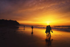 People walking on beach at sunset. People walking on the beach at sunset royalty free stock photos