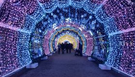 People walking through beautiful bright bluee and violet light tunnel in Moscow park during new year illumination stock photo