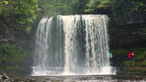 People walking behind by Sgwd yr Eira Waterfall, Brecon Beacons National Park stock video footage