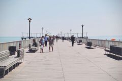 People Walking on a Beige Concrete Bridge Pathway Near Seashore during Daytime Stock Images