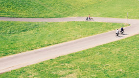 People Walking and Biking on the Concrete Roadway in Middle of Green Plain Fields Royalty Free Stock Images