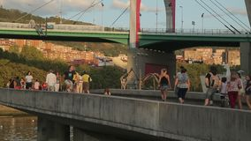 People walking bridge across river, viewing street art paintings, active life. Stock footage stock footage
