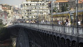 People walking on bridge near tram. People walking through bridge Ponte Luis I near vehicle in Porto, Portugal stock video footage