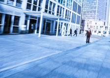 People walking in the business district, with skyscrapers. Royalty Free Stock Image