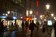 People walking in the the city on a foggy night. A thick fog is laying over the city at night, with lot of mood and shadows and a colorful glow from the signs royalty free stock photography